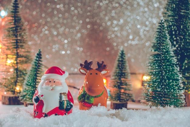 Papá noel y renos están parados en un montón de nieve en la noche silenciosa con árbol de navidad y adornos