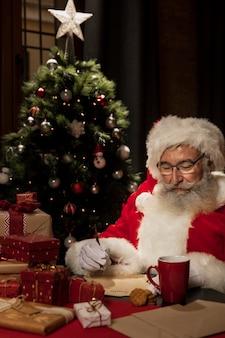 Papá noel rodeado de regalos de navidad