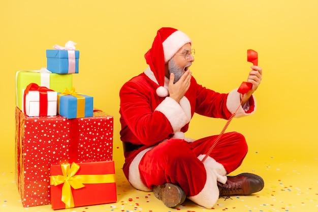 Papá noel sentado en el piso con teléfono de línea terrestre retro, felicitaciones de navidad, cubriendo la boca