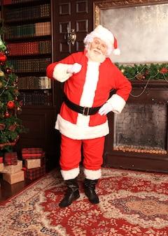 Papá noel tradicional de pie junto a la chimenea y el árbol de navidad en una habitación.