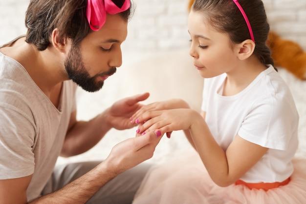 Papá pinta uñas de pequeñas hijas con un esmalte.