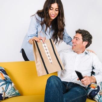 Papá recibe un regalo de su hija en el sofá