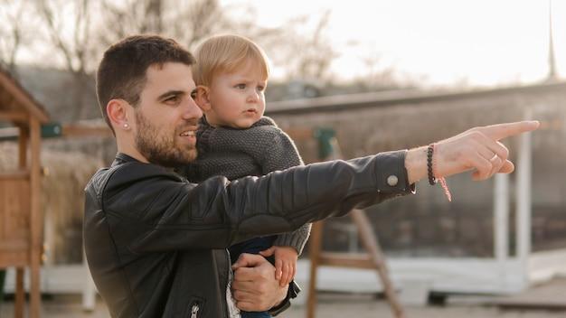 Papá señalando y sosteniendo a su hijo en el patio de recreo