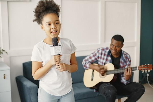 Papá está sentado con una guitarra e hija con un micrófono.
