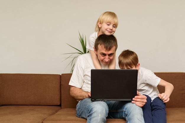 Papá sentado en el sofá con la computadora portátil y tratando de trabajar, y dos niños interfieren con él. concepto independiente de trabajo remoto