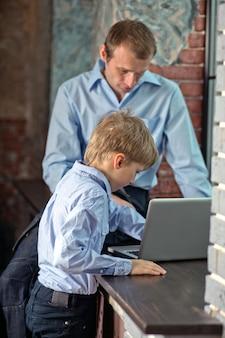 Papá se sienta en el alféizar de la ventana y le enseña a su hijo a trabajar en la computadora