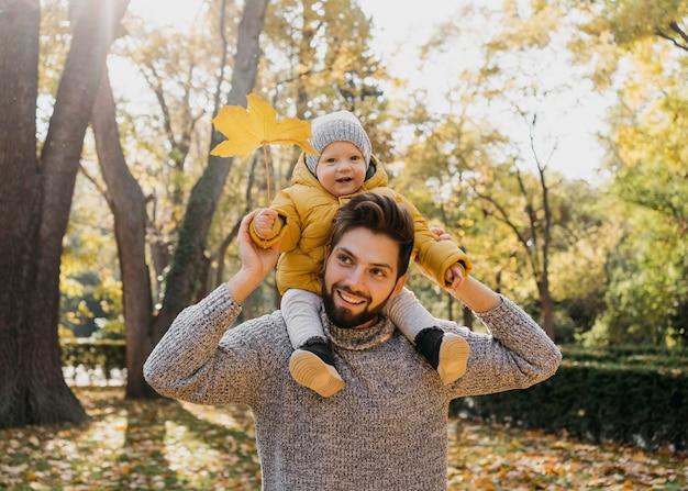 Papá sonriente con su bebé afuera en la naturaleza