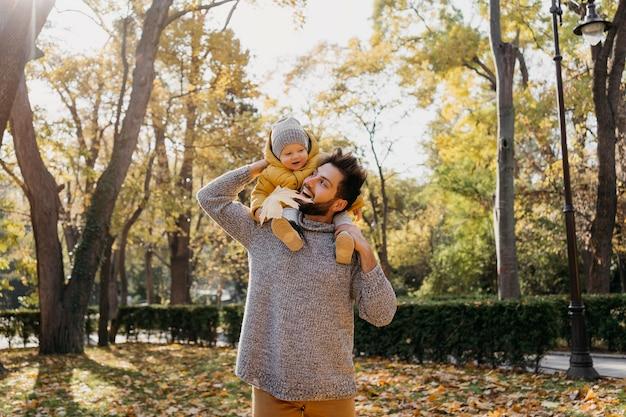 Papá sonriente con su bebé afuera