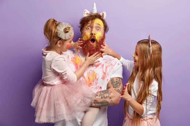 Papá sorprendido y dos niñas juegan juntos en casa, pintan caras con acuarelas, se divierten, muestran las manos pintadas en colores brillantes, aisladas sobre una pared púrpura. retrato familiar. paternidad