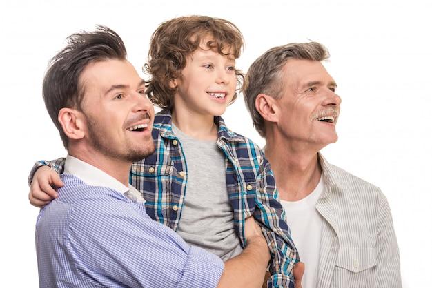 Papá sostiene a su hijo en sus brazos, el abuelo está cerca.