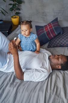 Papá con su hija acostada en la cama de vacaciones