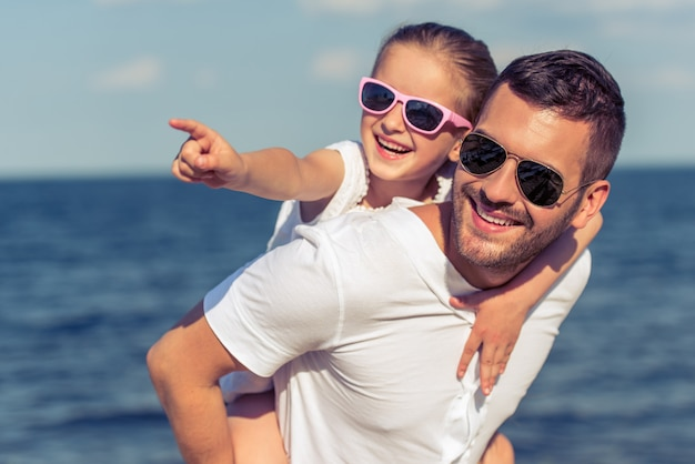 Papá y su pequeña hija en lentes de sol están mirando hacia otro lado.