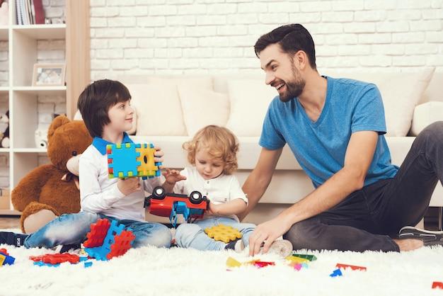 Papá y sus dos hijos juegan juguetes en casa.