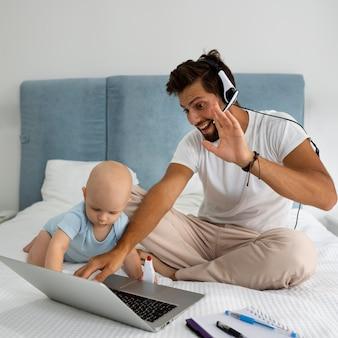 Papá trabajando desde casa durante la cuarentena con el niño