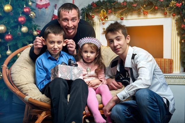 Papá con tres hijos cerca del árbol junto a la chimenea con regalos.