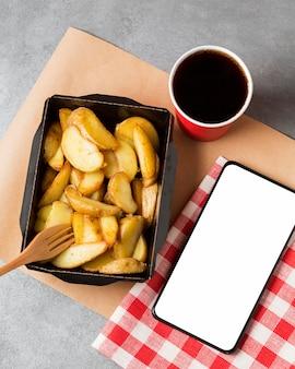 Papas fritas de alto ángulo y coca cola con teléfono en blanco