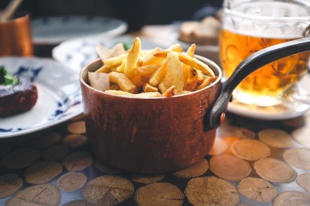 Papas fritas con bistec y cerveza