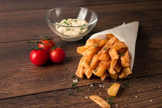 Papas fritas, en una bolsa de papel sobre un fondo marrón de madera, primer plano. comida rápida.