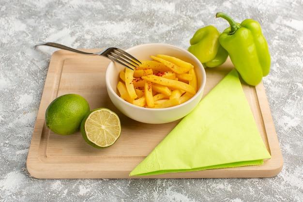 Papas fritas dentro de la placa blanca junto con pimiento verde y limón sobre gris