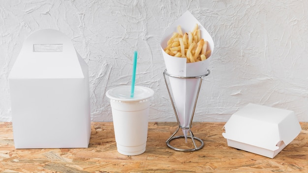 Papas fritas; disposición de vasos y paquetes en escritorio de madera.
