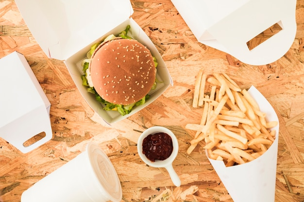 Papas fritas; hamburguesa y papas fritas sobre fondo de madera con texto