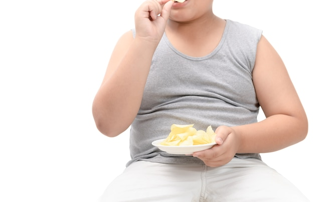 Papas fritas en la mano del niño gordo obeso aislado