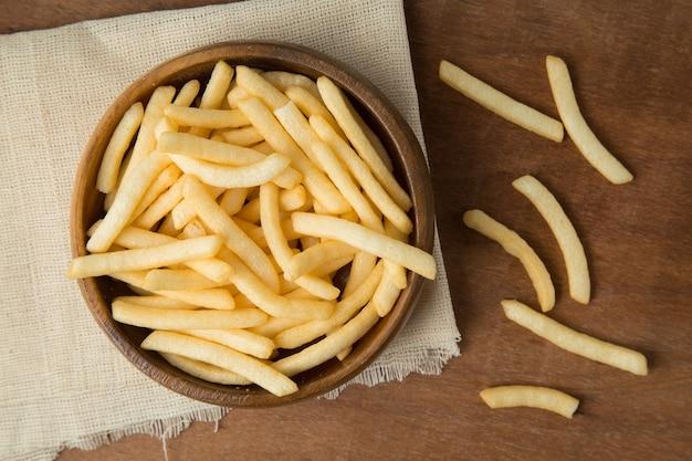 Papas fritas o patata frita en el tazón de madera que pone en el lino y el fondo de madera.