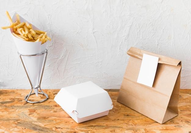 Papas fritas y paquete de comida se burlan de arriba en la mesa de madera