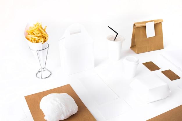 Papas fritas; paquete; hamburguesa y maqueta de vaso desechable sobre fondo blanco