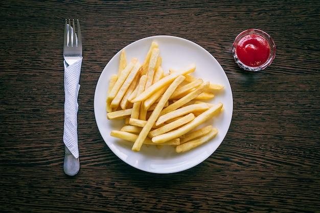 Papas fritas en un plato blanco con salsa de tomate