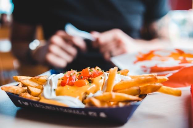 Papas fritas con salsa en bandeja desechable
