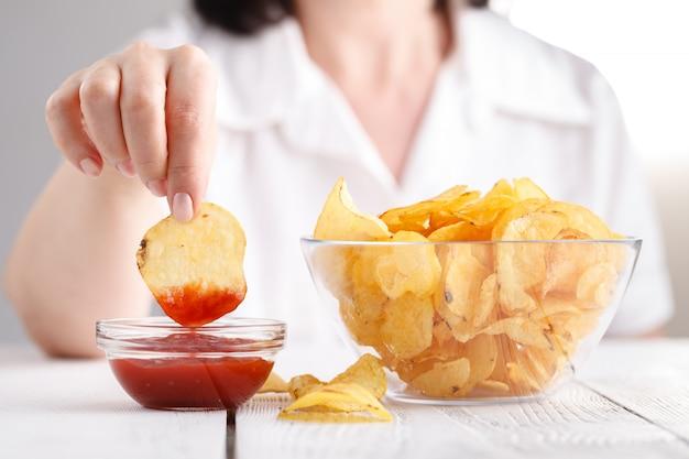 Papas fritas con salsa de tomate, las mujeres comen comida chatarra