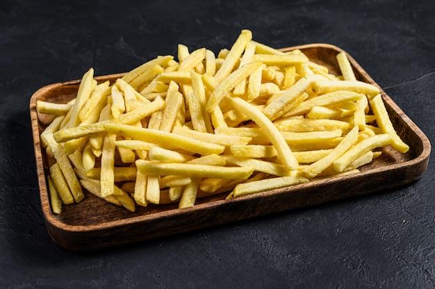Papas fritas en un tazón de madera. papas orgánicas fondo negro. vista superior.