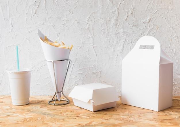 Papas fritas con vaso de comida y paquete de comida en superficie de madera