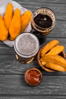 Papas fritas y vasos de cerveza de vista superior
