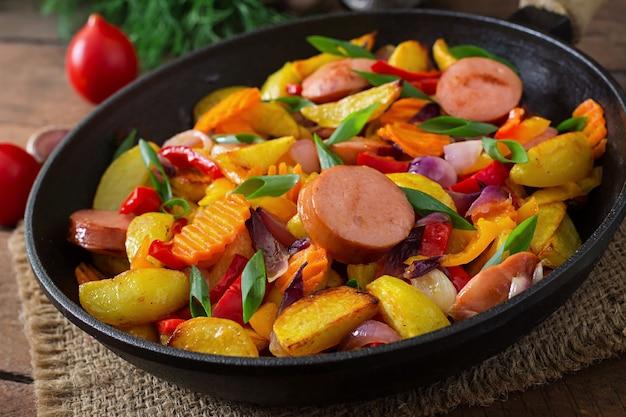 Papas fritas con verduras y salchichas.