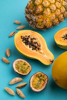 Papaya cortada madura, piña, melón, maracuyá, almendras sobre fondo azul pastel. vista lateral,