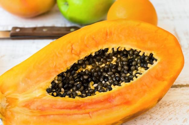 Papaya jugosa muy madura cortada por la mitad en la mesa de la cocina de madera con cítricos, manzanas, vista superior