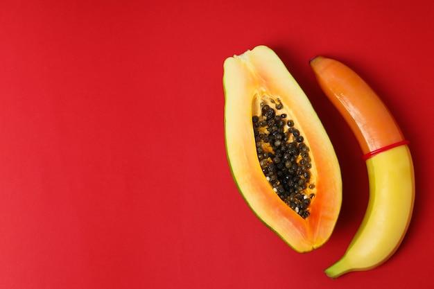 Papaya y plátano con condón sobre fondo rojo.