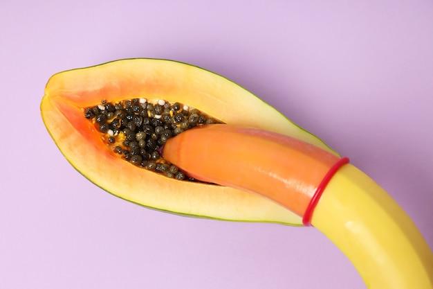 Papaya y plátano con condón sobre fondo violeta