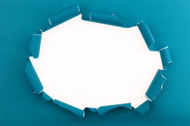Papel abierto rasgado azul sobre fondo blanco, espacio para su mensaje en papel rasgado blanco.