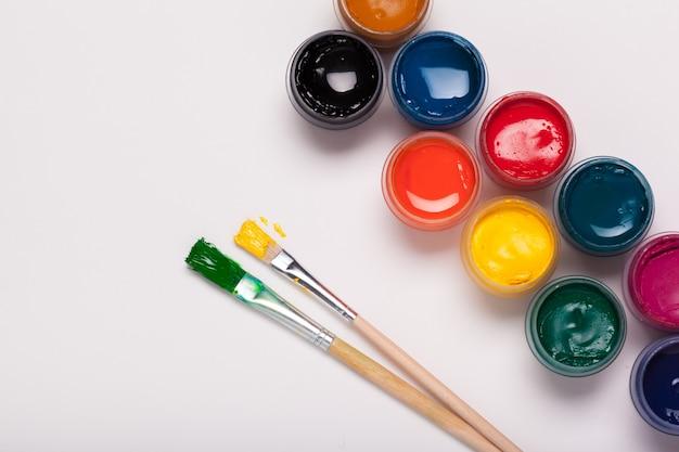 Papel, acuarelas, pincel y algunas cosas de arte de cerca vista superior
