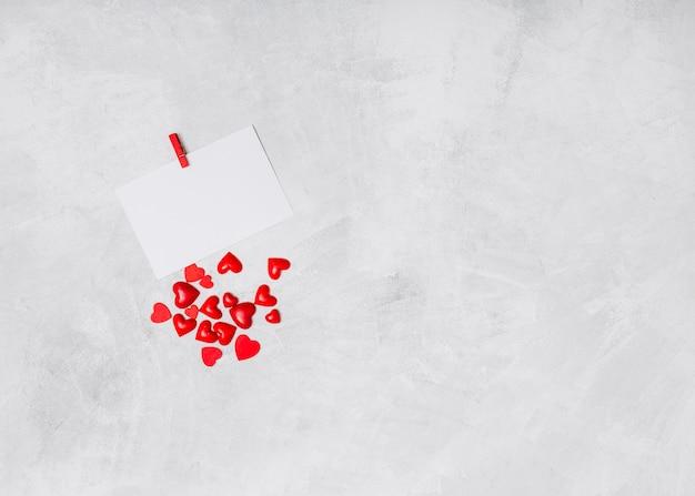 Papel con alfiler y adorno de corazones.