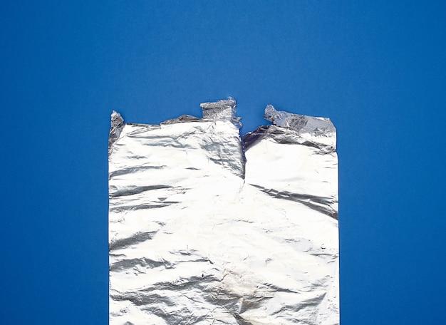 Papel de aluminio gris para hornear y envasar alimentos sobre un fondo azul.