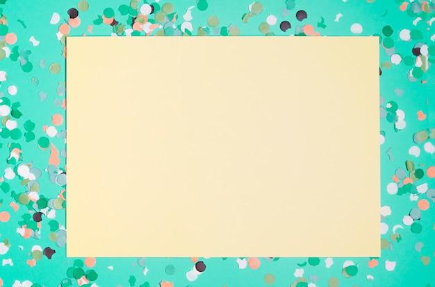 Papel amarillo en blanco con confeti de colores sobre fondo verde