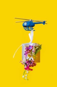 Papel amarillo caja regalo juguete entrega helicóptero fondo amarillo mosca flores