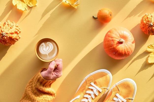 El papel amarillo de otoño yacía plano con la mano con una taza de café con leche de calabaza, calabazas naranjas, zapatos y decoraciones