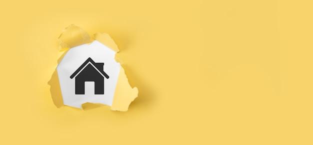Papel amarillo rasgado con casa sobre fondo blanco. seguro de propiedad y concepto de seguridad.