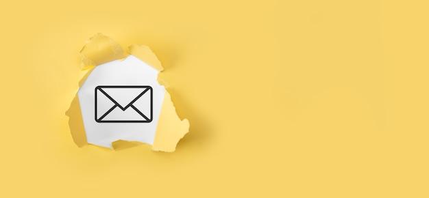 Papel amarillo rasgado con icono de correo electrónico de carta en superficie blanca