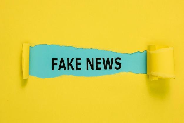 Papel amarillo rasgado y palabras falsas